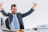 Cheerful businessman gesturing thumbs up at office desk