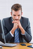Thoughtful businessman sitting at office desk