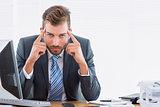 Elegant businessman with headache at office desk