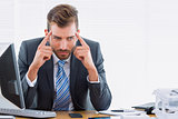 Businessman with severe headache at office desk