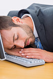 Businessman resting with head over keyboard at desk