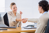 Smartly dressed women shaking hands in business meeting