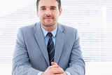 Smiling confident businessman at office desk