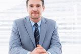 Smiling confident businessman at office desk