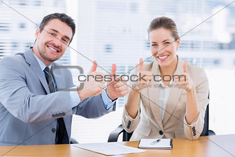 Businessman and woman gesturing thumbs up