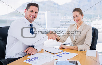 Smartly dressed colleagues shaking hands in a business meeting