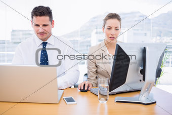 Smartly dressed colleagues using computer and laptop