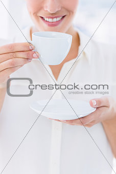 Mid section of a businesswoman with tea cup