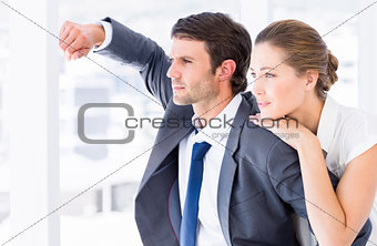 Smartly dressed business couple looking away in office
