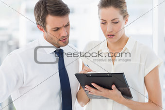 Smartly dressed colleagues using digital tablet