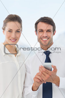 Smartly dressed colleagues with a mobile phone