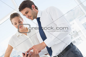 Smartly dressed colleagues looking at mobile phone