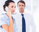 Woman on call with colleague in background at office