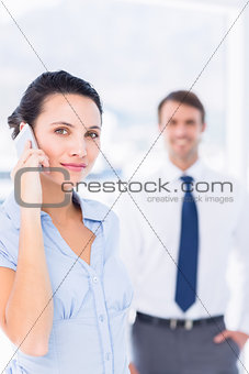 Woman on call with male colleague in background