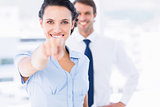 Happy woman pointing at camera with colleague in background