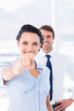 Woman pointing at camera with colleague in background