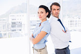Young business couple standing with arms crossed