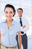 Smiling businesswoman with male colleague in background