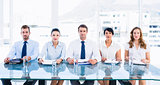 Smartly dressed executives sitting in row at desk