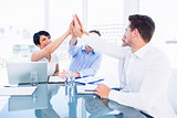 Executives giving high five in a business meeting