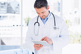 Concentrated male doctor using digital tablet