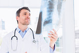 Serious male doctor examining xray