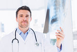 Portrait of a male doctor examining xray