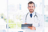 Portrait of a confident male doctor with clipboard