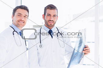 Portrait of two male doctors examining xray