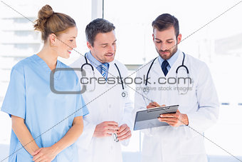 Doctors and female surgeon reading medical reports