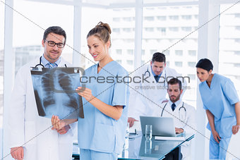 Doctors examining xray with colleagues using laptop behind