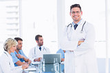 Smiling doctor with colleagues in meeting