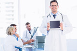 Doctor holding digital tablet with colleagues in meeting