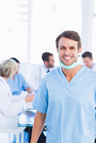 Smiling male surgeon with colleagues in meeting