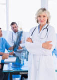 Smiling female doctor with colleagues in meeting
