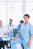 Serious female surgeon with colleagues in meeting