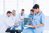 Female surgeon looking at reports with colleagues in meeting