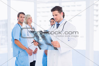 Doctor examining xray with colleagues standing behind