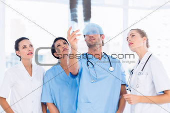 Group of doctors and surgeons examining xray