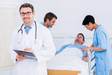 Doctor holding reports with patient and surgeon in background