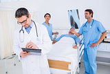 Doctors holding reports by patient at hospital