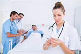 Doctor holding syringe with colleagues and patient at hospital