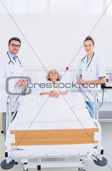 Doctors visiting a female patient in hospital