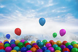 Many colourful balloons above snow