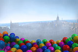 Many colourful balloons in room with city on wall