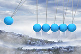 Newtons cradle above city in mountains
