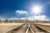Train tracks leading to city under blue sky
