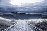 Stony path leading to large misty mountains