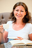 woman with a cup of coffee smiling