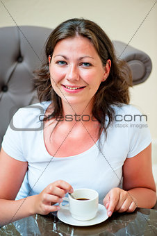 beautiful woman stirs sugar in a cup of coffee